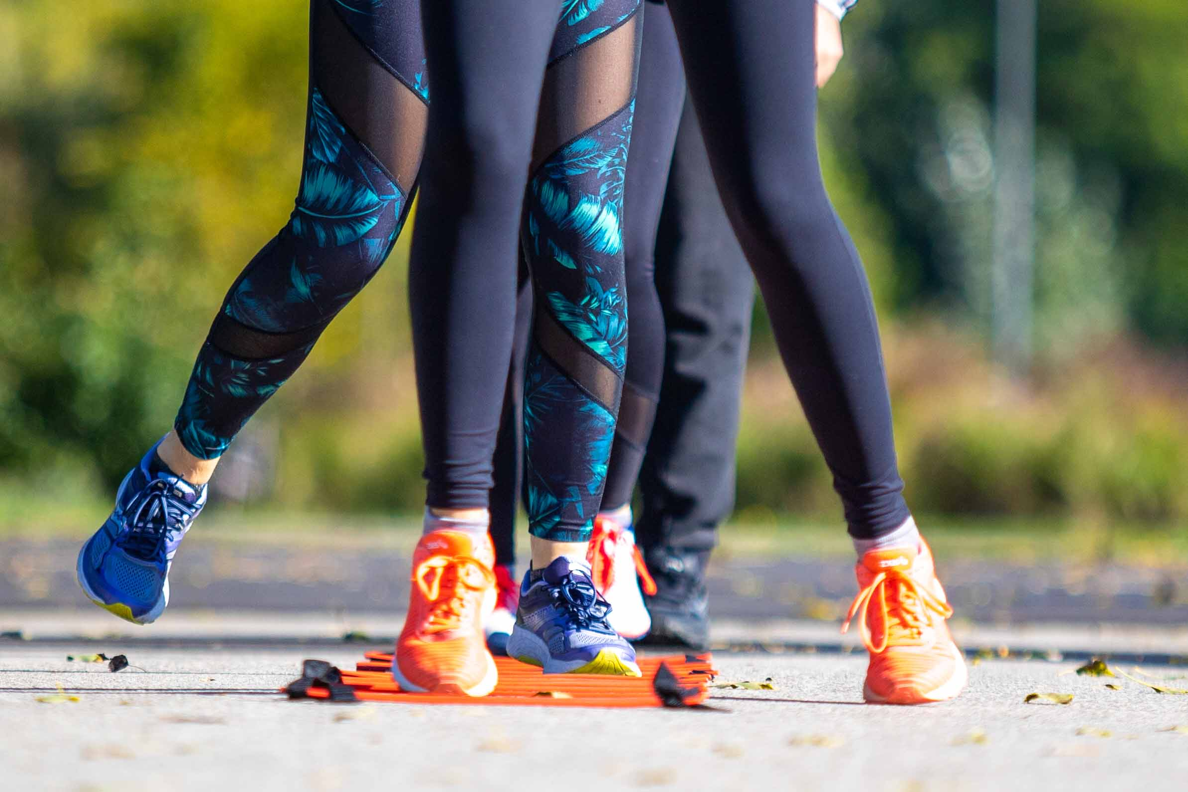 Laufgruppe beim Lauftechniktraining im Park, Beine, die über die Laufleiter laufen
