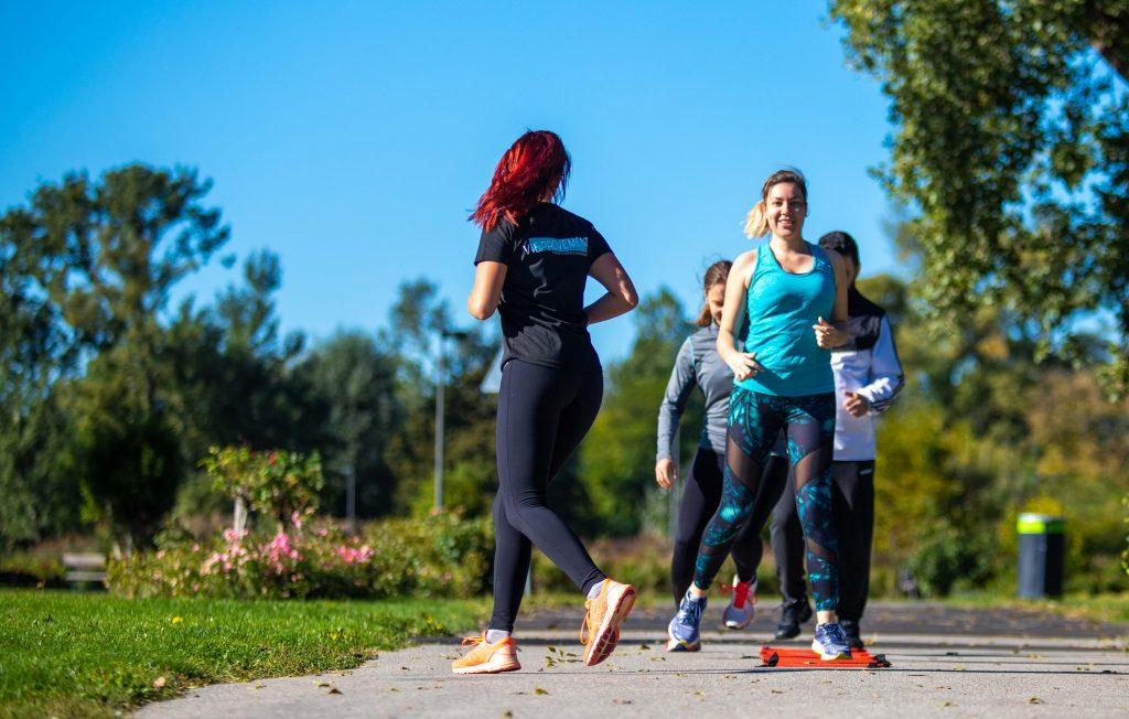 Laufgruppe beim Lauftechniktraining mit Laufleiter im Park