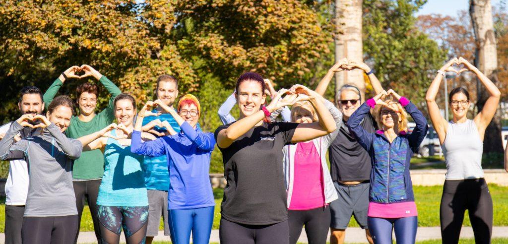 Gruppe von Läufern stehend, halten die Hände in die Luft und bilden mit den Fingern Herzen