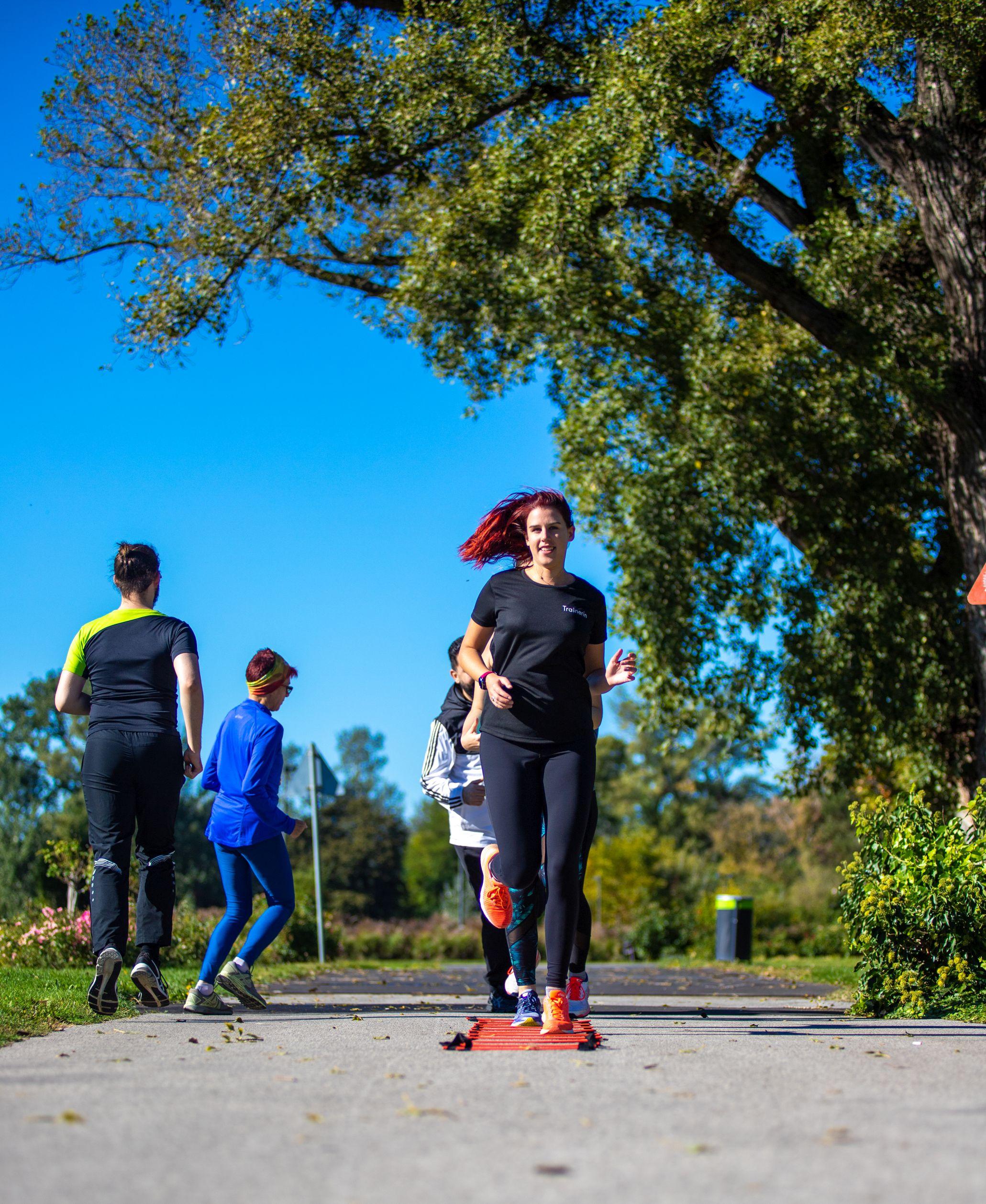 Gruppe von Läufern bei Übungen mit der Laufleiter im Park